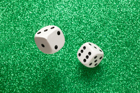 rolling dice: Rolling white dice over green glittering surface