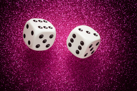 rolling dice: Rolling white dice over purple glittering surface