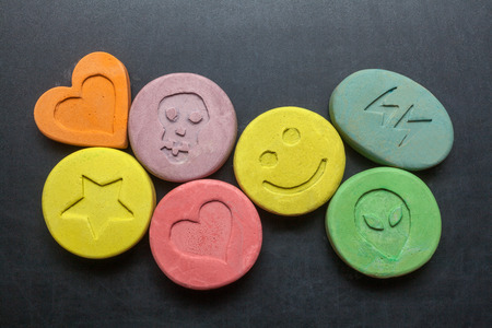 psychoactive: Ecstasy tablets on black background Stock Photo