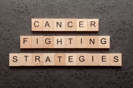 fighting cancer: Wooden letters spelling CANCER FIGHTING STRATEGIES on black background
