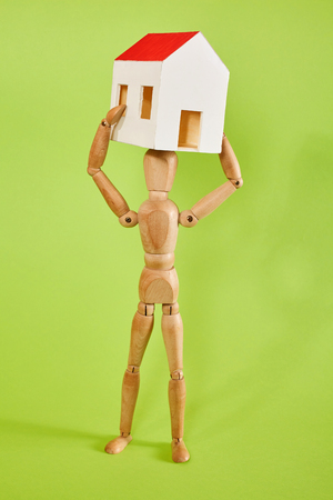 jointed: Dummy carrying small house on green background