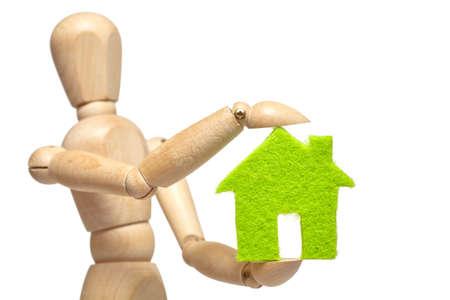 marioneta de madera: marioneta de madera tiene la pequeña casa verde sobre fondo blanco