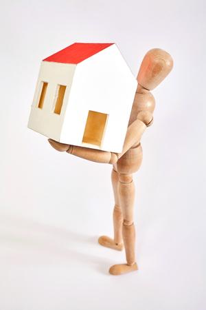 marioneta de madera: Maniquí llevando pequeña casa en el fondo blanco Foto de archivo