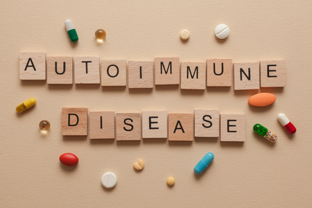 autoimmune: The word autoimmune disease formed with wooden letters and pills around Stock Photo