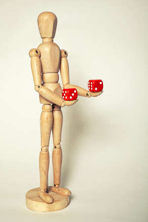 Wooden puppet holds dice on white background