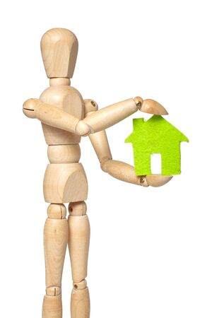 marioneta de madera: Wooden puppet holds small green house on white background