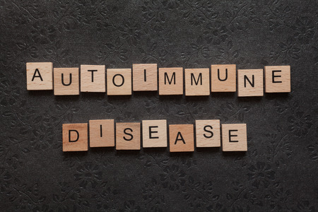 autoimmune: The word autoimmune disease formed with wooden letters on dark background