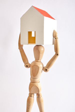 Dummy carrying small house on white background Stock Photo