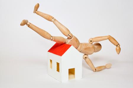 marioneta de madera: Maniquí cae desde pequeña casa en el fondo blanco