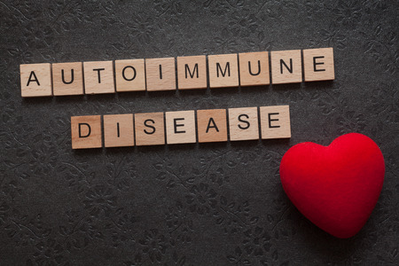 The word autoimmune disease formed with wooden letters and a heart on dark background
