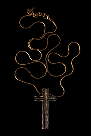 personal ornaments: Golden chain necklace with cross on blackground Stock Photo