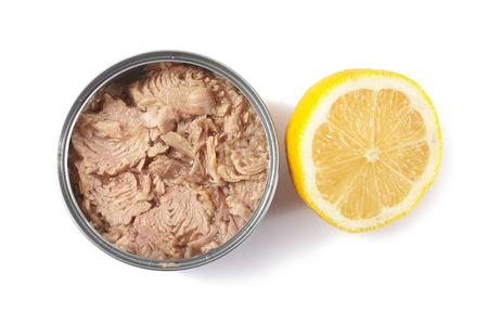 Open tuna tin with half lemon on a white background