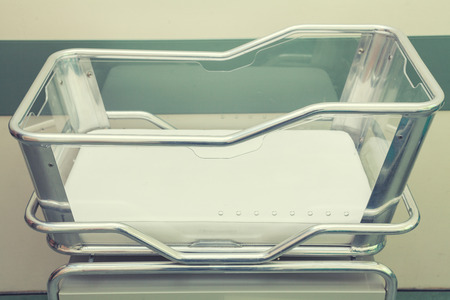 Stainless Steel Hospital Baby Cot with green background Stock Photo