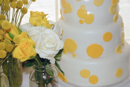 yellow: Wedding cake with yellow polka-dots and vases of roses Stock Photo