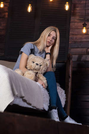 Young beautiful woman embraced teddy bear sitting on bed in bedroom. beautiful interior with vintage lamps
