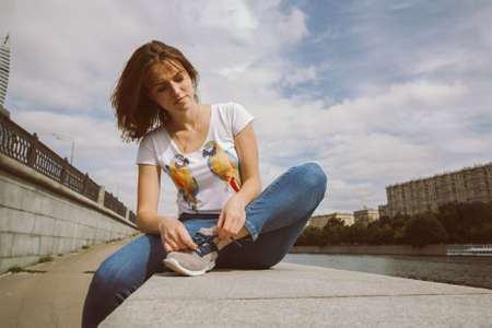 Woman tying sport shoes sitting on the stone parapet near the river. portrait of pretty girl in blue jeans tying shoelaces on the old embankment Stock fotó
