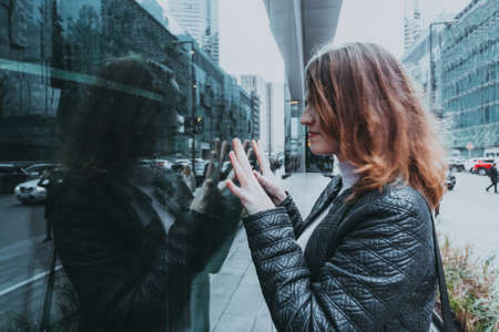 woman in black jacket standing on the street and looking at shop exposition in glass case