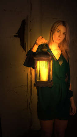Woman with Vintage Lantern walks in the dark in an abandoned room. Mysterious blonde woman in elegant dress holding lantern with candle in scary room Imagens