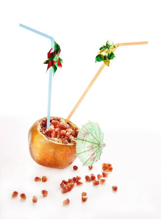 Fresh and juicy pomegranate fruit with pipes for drinking juice photo