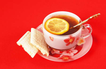 Cup of black tea with a lemon on a red cloth photo