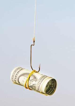 The concept. Dollars as a bait hang on a hook against the blue sky