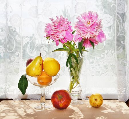 Still Life. Bouquet of peonies and fresh fruit in a vase on the table photo