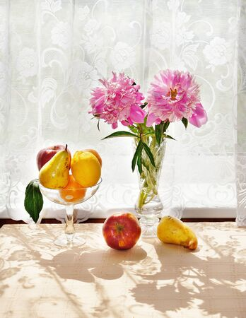 Still Life. Bouquet of peonies and fresh fruit in a vase on the table Stock Photo - 9798464