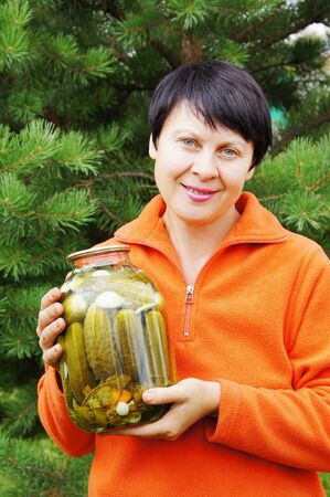 The woman-gardener holds banks with the preserved cucumbers photo