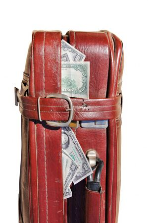 Dollars stick out of an old road bag Stock Photo - 10299875