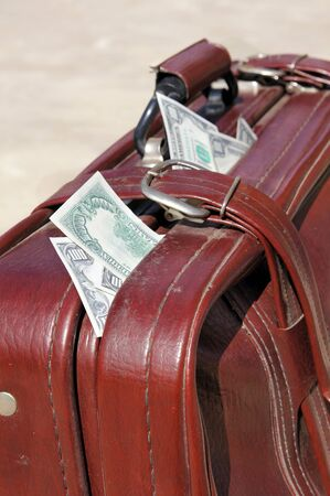 Dollars stick out of an old road bag Stock Photo - 10299872