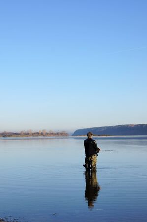 The fisherman is fishing on the river with a spinning photo