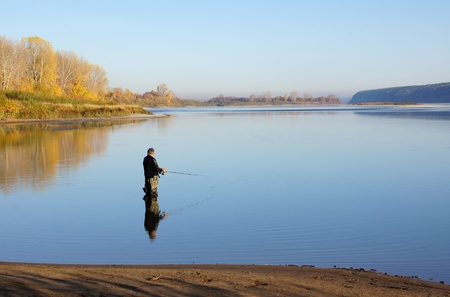 The fisherman is fishing on the river with a spinning Stock Photo - 10718338