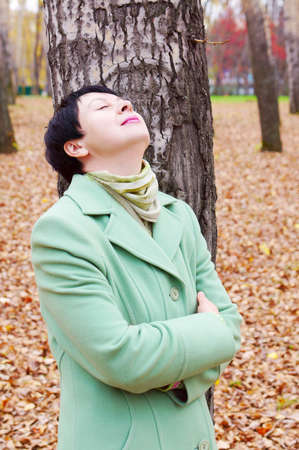 The young beautiful woman has a rest in autumn park photo