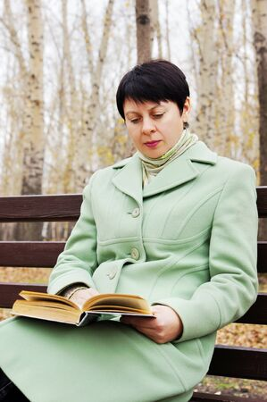 The young woman reads the book in autumn park photo