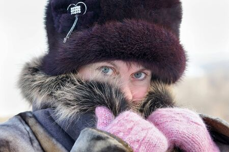 Cold weather. The woman muffles up in a fur collar photo