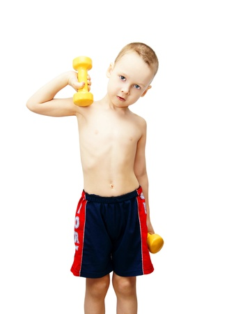 The little boy goes in for sports with dumbbells Stock Photo