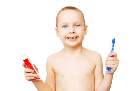 The little boy shows a tooth-brush and a tube with tooth-paste photo