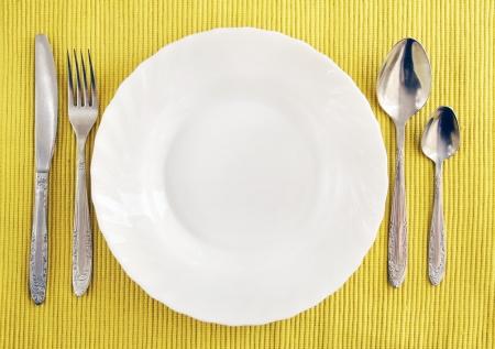legen: Wei�e leere Teller mit Gabel, L�ffel und Messer auf einem gelben Tischdecke
