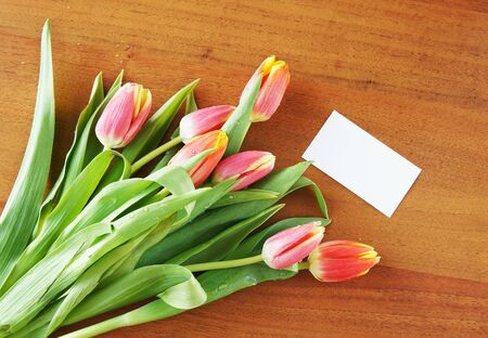 Bouquet of tulips on the table and empty white card Stock Photo - 12721655