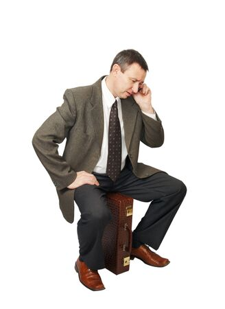 Businessman sits on suitcase and talks by phone Stock Photo - 12721746