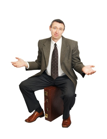 Confused man sits on suitcase Stock Photo