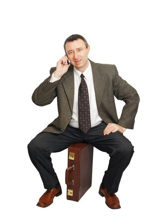 Man sits on the bag and talks by phone Stock Photo - 12721766