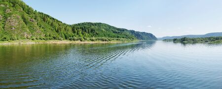 Wide panorama of a river and the forested mountains photo