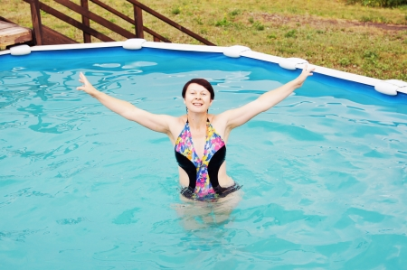 Woman is swimming in a little outdoor pool photo
