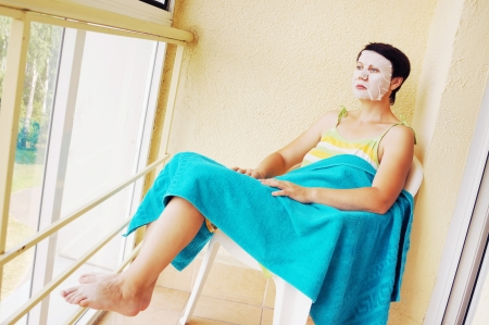 Woman has a rest with a cosmetic mask on her face photo