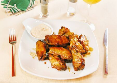Chicken wings in wine sauce on a plate photo