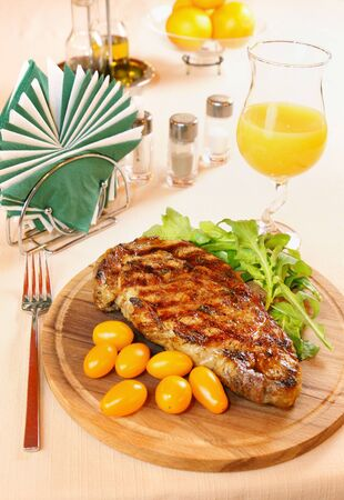 Ribeye steak on a wooden plate photo