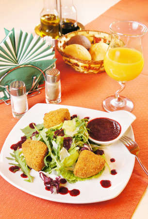 pepperbox: Fried cheese Camembert with cranberry sauce on a laid table Stock Photo