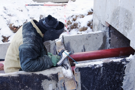 Welder works at a construction site in the winter photo