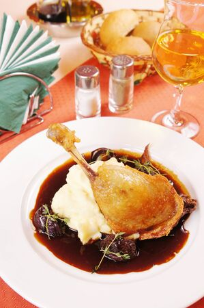 Confit of duck with mashed potatoes on a laid table photo